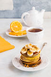 Stack of homemade pancakes with banana, maple syrup and walnuts on vintage plate. Fork, fresh sliced lemon, cup of tea and teapot, white and gray concrete royalty free stock photo