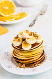 Stack of homemade pancakes with banana, maple syrup and walnuts on vintage plate. Fork, fresh sliced lemon, white and gray concrete background stock photography