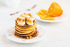 Stack of homemade pancakes with banana, maple syrup and walnuts on vintage plate. Fork, fresh sliced lemon, white and gray concrete background royalty free stock photo