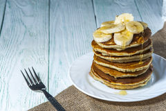 Stack of homemade pancakes with banana slices and honey on white plate with fork and linen napkin on wooden background. Stock Photography
