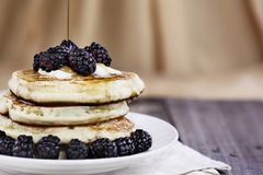 Pancakes Berries and Syrup Being Poured royalty free stock image