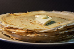 Stack of homemade pancakes with butter and honey on brown plate on rustic background. Russian holiday pancake week. Focus on panca. Kes. Horizontal view Royalty Free Stock Photography