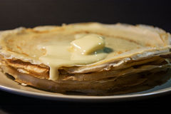 Stack of homemade pancakes with butter and honey on brown plate on rustic background. Russian holiday pancake week. Focus on panca. Kes. Horizontal view Royalty Free Stock Photo