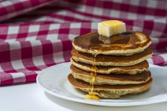 Stack of homemade pancakes with butter and honey on white plate with checkered napkin. Royalty Free Stock Image