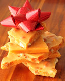 Stack of Homemade Peanut Brittle with Red Bow. Traditional homemade peanut brittle displayed on a wood tray with a red bow. Empty space provided on right Stock Photography