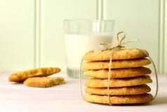 A stack of homemade peanut butter cookies tied with twine. Broken biscuit and glass of milk. Stock Image