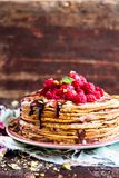 Stack of homemade thin pancakes or crepes or pancake cake with chocolate sauce, fresh raspberry, pistachios nuts decorated with fr. Esh mint leaves on a plate Royalty Free Stock Photos