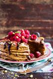 Stack of homemade thin pancakes or crepes or pancake cake with chocolate sauce, fresh raspberry, pistachios nuts decorated with fr. Esh mint leaves on a plate Royalty Free Stock Images