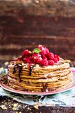 Stack of homemade thin pancakes or crepes or pancake cake with chocolate sauce, fresh raspberry, pistachios nuts decorated with fr. Esh mint leaves on a plate Stock Photos