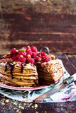 Stack of homemade thin pancakes or crepes or pancake cake with chocolate sauce, fresh raspberry, pistachios nuts decorated with fr. Esh mint leaves on a plate Royalty Free Stock Image