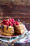 Stack of homemade thin pancakes or crepes or pancake cake with chocolate sauce, fresh raspberry, pistachios nuts decorated with fr. Esh mint leaves on a plate Stock Images