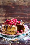 Stack of homemade thin pancakes or crepes or pancake cake with chocolate sauce, fresh raspberry, pistachios nuts decorated with fr. Esh mint leaves on a plate Royalty Free Stock Photography