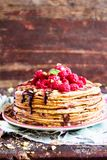 Stack of homemade thin pancakes or crepes or pancake cake with chocolate sauce, fresh raspberry, pistachios nuts decorated with fr. Esh mint leaves on a plate Stock Photo