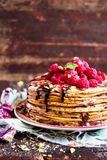 Stack of homemade thin pancakes or crepes or pancake cake with chocolate sauce, fresh raspberry, pistachios nuts decorated with fr. Esh mint leaves on a plate Stock Photography