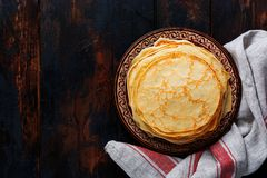 Stack of homemade thin pancakes with pieces of butter, milk and honey on old rustic ceramic plate. royalty free stock photography