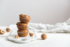 Stack of Homemade vegan banana walnut muffins. Side view, copy space royalty free stock photo