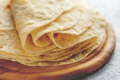 Stack of homemade wheat flour tortilla wraps on wooden cutting board. Stack of homemade wheat flour tortilla wraps for burrito close-up on wooden cutting board stock photography