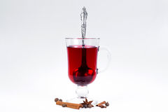 Stack of hot mulled wine with apples and oranges, cloves and vanilla sticks on a white background. Hot Christmas drink. Stock Photos