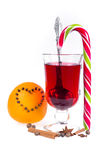 Stack of hot mulled wine with apples and oranges, cloves and vanilla sticks on a white background. Hot Christmas drink. Royalty Free Stock Images