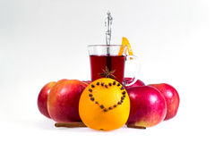 Stack of hot mulled wine with apples and oranges, cloves and vanilla sticks on a white background. Hot Christmas drink. Royalty Free Stock Photo