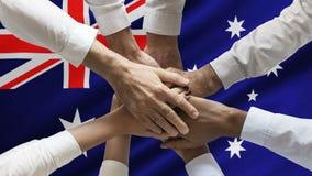 Stack of human hands over animated waving Australian flag