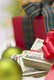 Stack of Hundred Dollar Bills with Bow Near Christmas Ornaments. Stack of One Hundred Dollar Bills with Red Bow Near Green Christmas Ornaments and Wrapped Gift Royalty Free Stock Images