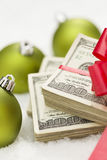 Stack of Hundred Dollar Bills with Bow Near Christmas Ornaments Royalty Free Stock Image