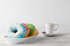Stack of iced donuts with coffee cup on table Royalty Free Stock Photography