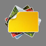 Stack of images. Overhead view of images or photographs in stack with blank yellow sticker on top Stock Photo