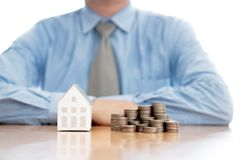 Stack of increasing coins and house model with businessman royalty free stock photos