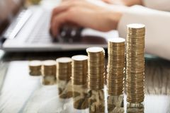 Stack Of Increasing Coins On Office Desk. A Businessperson`s Hand On Laptop With Stack Of Increasing Coins On Office Desk Royalty Free Stock Images