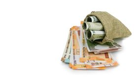 Stack of Indian Rupee currency note and stuffed in burlap bag on white background stock image