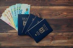 Stack of israeli money bills of 200 shekel and israeli passport stock photos