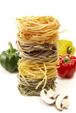 Stack of italian pasta, tagliatelle, mushroom slices and bell peppers Royalty Free Stock Images