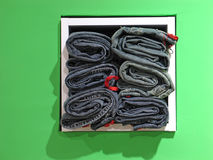 Stack of jeans. In green store display Royalty Free Stock Images