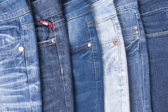 Stack of jeans. Jeans in different colors lying on the table stock photos