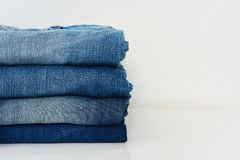 Stack of blue jeans isolated on white background. Copy space abstract apparel black bluejeans bottoms cloth clothes clothing color corner dark denim design royalty free stock photo
