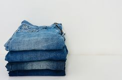 Stack of blue jeans on white background. Copy space abstract apparel black bluejeans bottoms cloth clothes clothing color corner dark denim design fabric royalty free stock photography
