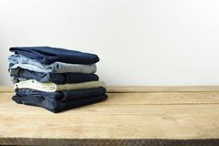 Stack of jeans in a living room setting with a white wall background. royalty free stock photo