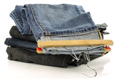 Stack of jeans and one with clothes hanger Royalty Free Stock Photos
