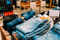 Stack Of Jeans On Shelves In Store Of Shopping Center.  stock photo