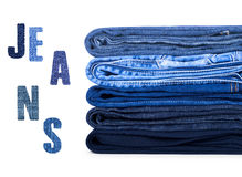 Stack of jeans on white background. And 'Jeans' inscription made from denim royalty free stock image