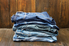 Stack of jeans on wooden background Stock Photo