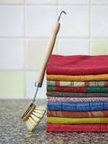 Stack of kitchen towels with dish-washing brush. Old fashion cleaning by hand. Colorful towels for drying dishes and a wooden brush Stock Image