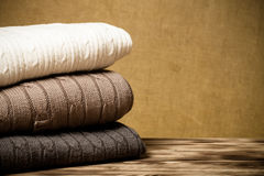 Stack of knitted clothes on wooden table opposite a defocused bu Stock Photography