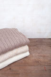 Stack of knitted clothes on wooden table opposite a tile wall Stock Image
