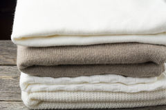 Stack of knitted sweaters on black background Stock Image