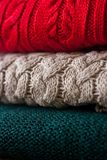 Stack of warm knitted sweaters close up. Cozy colorful background royalty free stock photos