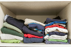 A stack of knitted warm woolen clothes in wardrobe close  Stock Photos