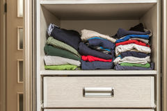 A stack of knitted warm woolen clothes in wardrobe close up Stock Image